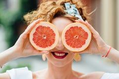 Девушка женщины подходящая держа 2 halfs грейпфрута Стоковое Изображение RF