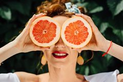 Девушка женщины подходящая держа 2 halfs грейпфрута Стоковое Фото
