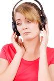 Девушка женщины унылая в музыке больших наушников слушая Стоковые Фото