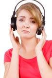 Девушка женщины унылая в музыке больших наушников слушая Стоковое Изображение