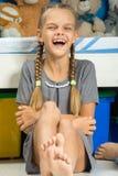 Девушка жизнерадостно смеется над сидеть кроватью стоковое изображение