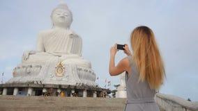 Девушка журналиста замедленного движения используя smartphone для того чтобы сделать фото из статуи Будды s в Таиланде акции видеоматериалы