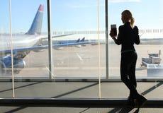 Девушка ждать ее полет в крупный аэропорт Стоковые Изображения