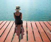 Девушка ждать на пристани смотря океан Стоковые Фото