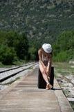 Девушка ждать с чемоданом завальцовки чистосердечным на доках стоковые фотографии rf