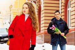 Девушка ждет ее парня, который стоит с цветками за ей Молодые пары идя совместно в город Стоковое фото RF
