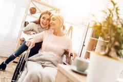 Девушка заботит для пожилой женщины дома Девушка едет женщина в кресло-коляске Стоковые Изображения RF