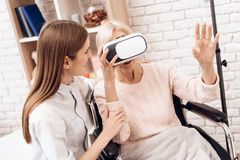 Девушка заботит для пожилой женщины дома Женщина использует виртуальную реальность Стоковое Фото