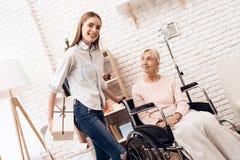 Девушка заботит для пожилой женщины дома Девушка приносить присутствующий для женщины Стоковые Изображения RF
