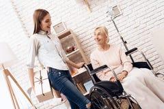 Девушка заботит для пожилой женщины дома Девушка приносить присутствующий для женщины Стоковая Фотография