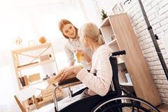 Девушка заботит для пожилой женщины дома Девушка приносит завтрак на подносе выпивая женщина сока Стоковое фото RF