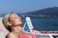 Девушка загорая на пляже моря Стоковая Фотография RF