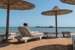 Девушка загорая на lounger на пляже На заднем плане пристань видима стоковое фото rf