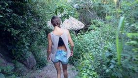 Девушка задней стороны идет вниз с каменных шагов среди плотного парка акции видеоматериалы