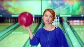 Девушка закручивает с шариком боулинга в ее руках стоковое изображение rf