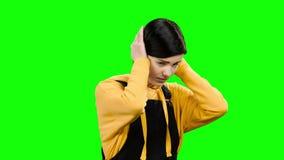 Девушка закрывает ее уши с ее руками зеленый экран акции видеоматериалы