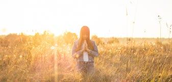 Девушка закрыла ее глаза, моля outdoors, руки сложенные в концепции молитве для веры, духовность и вероисповедание надежда, конце стоковые изображения