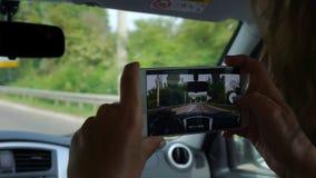 Девушка записывает видео на ее мобильном телефоне во время отключения автомобиля видеоматериал