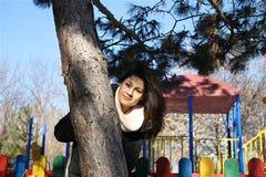 Девушка за деревом в парке Стоковые Фотографии RF