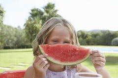 Девушка задерживая кусок арбуза перед стороной Стоковое Изображение