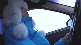 Девушка за колесом автомобиля танцует и поет Женщина управляет автомобилем в периоде снега зимы Независимые и свободные женщины акции видеоматериалы