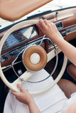 Девушка за колесом красивого ретро автомобиля Стоковые Изображения