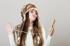 Девушка зимы наслаждаясь музыкой Стоковые Фото