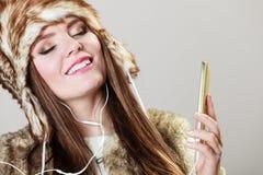 Девушка зимы наслаждаясь музыкой Стоковые Фотографии RF
