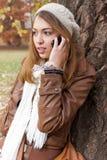 Девушка зноня по телефону в природе стоковое фото
