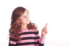 Девушка зрачка показывая что-то на белизне Стоковое Фото