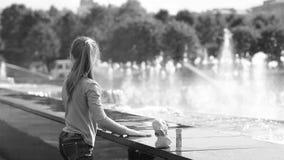 Девушка играет с водой около фонтана акции видеоматериалы