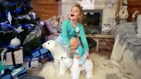 Девушка играет с куклой, играть ребенка около рождественской елки, ` s Eve Нового Года, времени чудес, игрушки рождества акции видеоматериалы