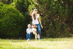Девушка играет с собакой в дворе Стоковая Фотография