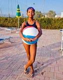 Девушка играет с шариком в бассейне на заходе солнца Стоковая Фотография