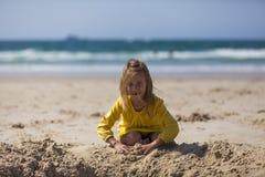 Девушка играя в песке на пляже Стоковые Изображения