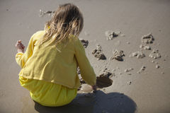 Девушка играя в песке на пляже Стоковое Изображение RF