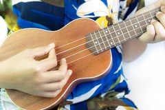 Девушка играя гавайскую гитару на белой предпосылке стоковые изображения rf