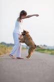 девушка играя детенышей щенка Стоковое фото RF