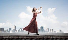 Девушка играя ее мелодию на файфе на дне лета ярком Мультимедиа стоковое фото rf