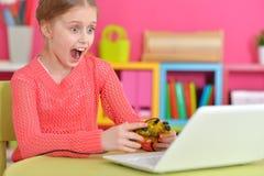 Девушка играя игру на компьтер-книжке Стоковое Фото
