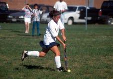 Девушка играя игру хоккея на траве средней школы стоковое фото rf