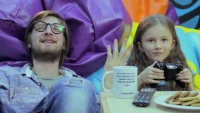 Девушка играя молодого человека консоли, наркомании игры, расточительствовать времени акции видеоматериалы
