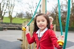 Девушка играя на взбираясь рамке в спортивной площадке школы стоковая фотография rf