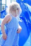 Девушка играя на скольжении на спортивной площадке Стоковые Изображения