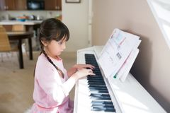 Девушка играя рояль и читая музыкальные примечания стоковое изображение rf