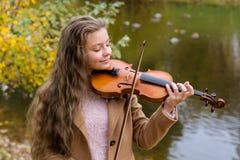 Девушка играя скрипку и усмехаясь в парке осени на озере стоковые изображения