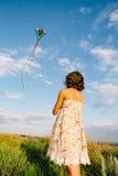 Девушка играя с змеем в поле Стоковые Изображения