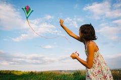 Девушка играя с змеем в поле Стоковая Фотография
