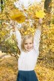 Девушка играя с листьями осени Стоковые Изображения