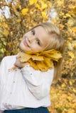 Девушка играя с листьями осени Стоковое Фото